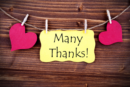 many thanks: The Words Many Thanks standing on a Yellow Label, framed by two red Hearts hanging on a Line on wooden Background Stock Photo