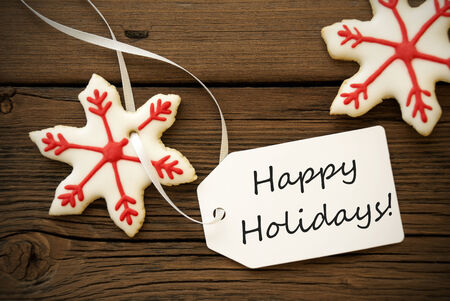 Christmas Star Cookies with red white Decoration and a Label on which stands Happy Holidays