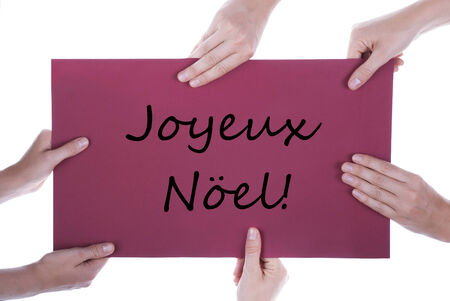 joyeux: Many Hands Holding a Red Sign with the French Words Joyeux Noel which means Merry Christmas