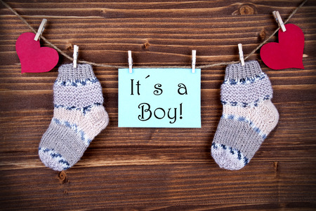 Blue Label with the Words Its a Boy and Baby Socks and red Hearts on a Line on wooden Background photo
