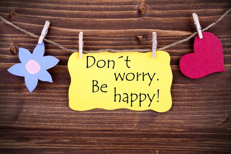 dont worry: Yellow  Label Dont Worry Be Happy On Wooden Background With Two Symbols Like Heart And Flower