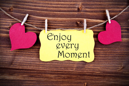 typographies: Yellow Lable Saying Enjoy Every Moment On Wooden Background Hanging On A Line, Two Red Heart Symbols; On Yellow Label; Background Is Old Fashion Stock Photo