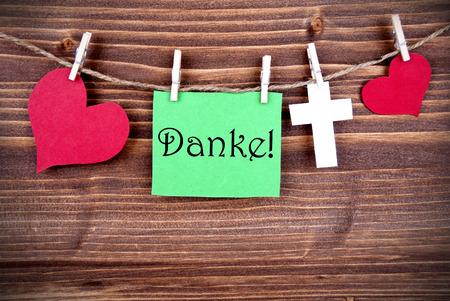 thankfulness: Green Tag Or Label With Hearts And Cross On A Line With The German Word Danke, Which Means Thanks On Wooden Background, Three Symbols, Vintage, Retro and Old Fashion Style With Frame