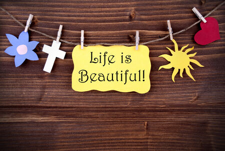 typographies: Yellow  Label Saying Life Is Beautiful On Wooden Background With Four Symbols Like Heart, Sun, Cross And Flower Stock Photo