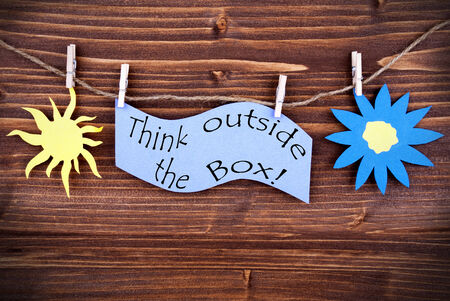 typographies: Light Blue Lable Saying Think Outside The Box On Wooden Background Hanging On A Line, One Blue Flower Symbol And One Yellow Sun Symbol Background Is Old Fashion