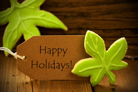 english text: Brown Organic Label With English Text Happy Holidays On Wooden Background With Two Leaf Cookies And Frame Stock Photo