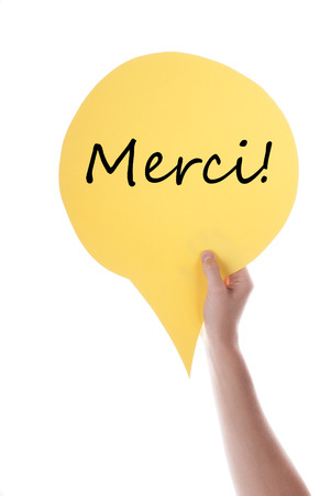 verticals: Hand Holding A Yellow Speech Balloon Or Speech Bubble With French Merci. Isolated Photo. Stock Photo