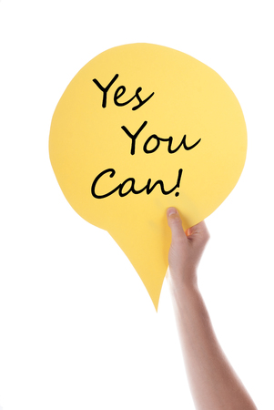 verticals: Hand Holding A Yellow Speech Balloon Or Speech Bubble With Yes You Can. Isolated Photo. Stock Photo