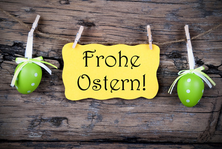 Ostern: Yellow Easter Label With German Text Frohe Ostern Which Means Happy Easter Hanging On A Line With Two Green Easter Eggs On Wooden Background, Vintage,  Old Fashion, Rustic Or Retro Style And Frame
