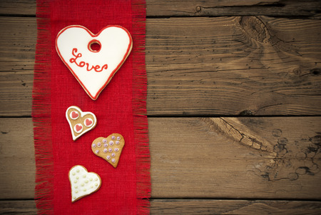 stile country: Tessuto rosso naturale Tovaglietta come texture con copia spazio su sfondo di legno con Country Style e quattro cuore Cookies With Love