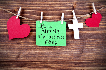 simple life: Green Tag Or Label With Hearts And Cross On A Line With Life Quote Life Is Simple Its Just Not Easy On Wooden Background, Three Symbols, Vintage, Retro And Old Fashion Style With Frame