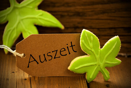 auszeit: Brown Organic Label With German Text Auszeit On Wooden Background With Two Leaf Cookies And Frame