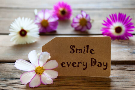 downtime: Brown Label With Life Quote Smile The Day With Purple And White Cosmea Blossoms On Wooden Background Vintage Retro Or Rustic Style Stock Photo