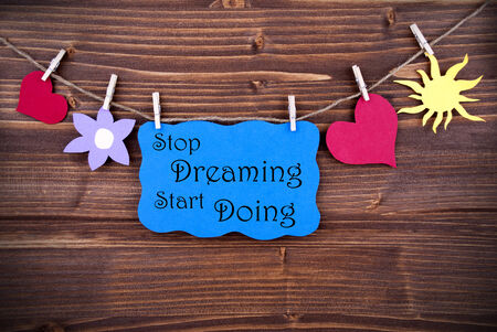 doings: Blue Tag Or Label With Hearts And Flower And Sun On A Line With Life Quote Stop Dreaming Start Doing On Wooden Background, Four Symbols, Vintage, Retro And Old Fashion Style With Frame Stock Photo