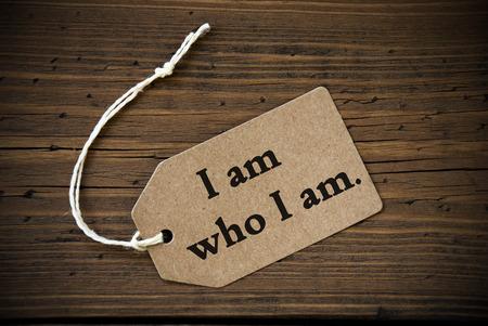 Nahaufnahme eines Brown Aufkleber mit weißem Farbband auf Holzuntergrund mit englischem Leben-Zitat Ich bin, wer ich bin Rahmen und Vintage-oder Retro-Stil Standard-Bild