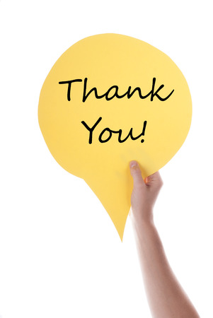 thankfulness: Hand Holding A Yellow Speech Balloon Or Speech Bubble With Thank You. Isolated Photo.