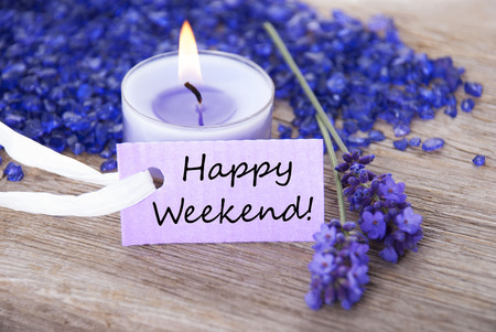 english text: Purple Label With Candle Light And Lavender Blossoms With English Text Happy Weekend On Wooden Background With White Ribbon