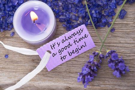 start: Purple Label bei Kerzenlicht und Lavendelbl�ten mit englischem Leben-Zitat ist immer eine gute Zeit zu beginnen auf Holzuntergrund mit wei�em Band Top View