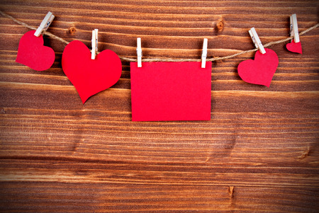 your text here: Red Tag Or Label With Four Hearts On A Line With Copy Space For Your Text Here On Wooden Background, Four Symbols, Vintage, Retro and Old Fashion Style With Frame