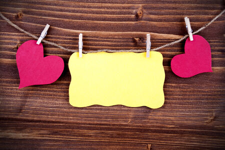Yellow Tag Or Label With Two Hearts On A Line With Copy Space Or Your Free Text Here On Wooden Background, Two Symbols, Vintage, Retro And Old Fashion Style With Frame photo