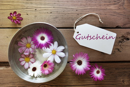 Silver Bowl With Label With German Text Gutschein With Purple And White Cosmea Blossoms On Wooden Background Vintage Retro Or Rustic Style photo