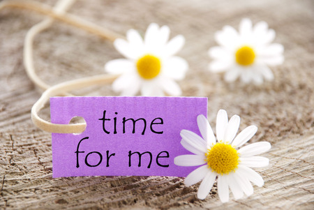 Purpel Label With White Ribbon And English Life Quote Time For Me With Three White Marguerite Blossoms On Wooden Background