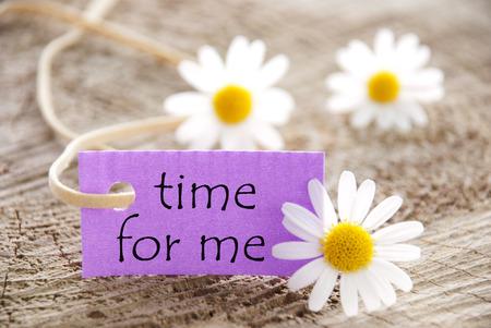 margriet: Purpel Label Met Witte Lint En Engels Life Quote tijd voor mij met drie witte Marguerite Bloesems Op Houten Achtergrond Stockfoto