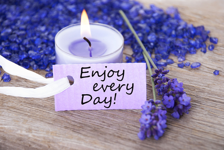 getting away from it all: Purple Label With Candle Light And Lavender Blossoms With English Life Quote Enjoy Every Day Wooden Background With White Ribbon