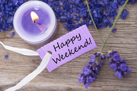 Purple Label With Candle Light And Lavender Blossoms With English Text Be Happy Weekend On Wooden Background With White Ribbon Top View photo