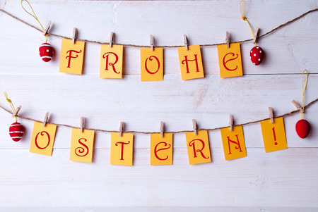 Ostern: Yellow Labels With Red German Text Frohe Ostern Which Means Happy Easter Hanging On A Line With Four Red And White Dotted And Striped Easter Eggs White Wooden Vintage Or Rustic Background For Easter Greetings