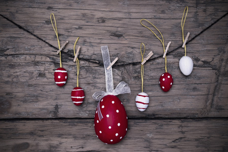 Five Red And White Easter Eggs And One Big Dotted Red Easter Egg With A Loop And Ribbon Hanging On A Line Which Are Dotted And Striped On Brown Wooden Vintage Or Rustic Background For Easter Greetings And Happy Easter Frame photo