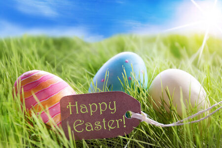 estival: Three Colorful Easter Eggs On Green Grass With Label With English Text Happy Easter And Sunny Blue Sky Stock Photo