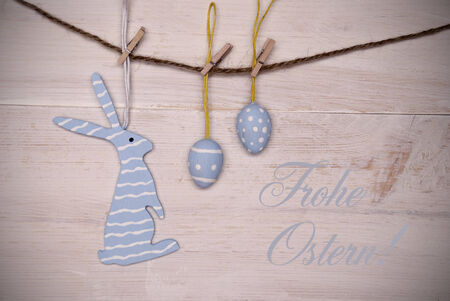 Ostern: One Blue Easter Bunny With Stripes Hanging On A Line With Two Blue Easter Eggs Which Are Dotted And Striped On White Wooden Vintage Or Rustic Background For Easter Greetings And Happy Easter With German Text Frohe Ostern Which Means Happy Easter Stock Photo