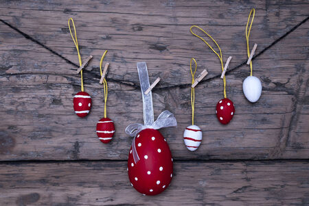Five Red And White Easter Eggs And One Big Dotted Red Easter Egg With A Loop And Ribbon Hanging On A Line Which Are Dotted And Striped On Brown Wooden Vintage Or Rustic Background For Easter Greetings And Happy Easter photo