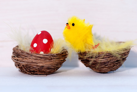 One Red Dotted Easter Eggs Laying In Easter Basket Or Nest And One Chick Sitting In Basket On White Wooden Background  As Easter Decoration Or Easter Greetings Vintage Or Old Fashion Style