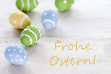Ostern: Blue Green And Yellow Easter Eggs Which Are Dotted And Striped On Wooden Vintage Background With German Text Frohe Ostern Which Means Happy Easter For Easter Greetings