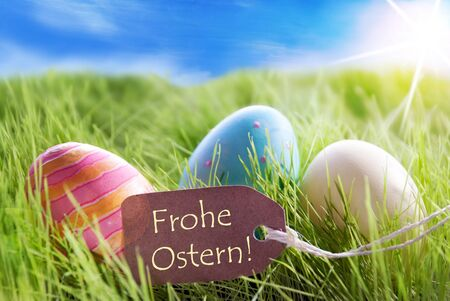 Ostern: Three Colorful Easter Eggs On Green Grass With Label With German Text Frohe Ostern Means Happy Easter And Sunny Blue Sky Stock Photo