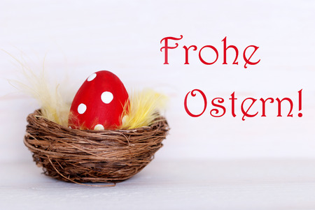Ostern: One Red Dotted Easter Eggs In Easter Basket Or Nest On White Wooden Background With German Text Frohe Ostern Means Happy Easter As Easter Decoration Or Easter Greetings Vintage Or Old Fashion Style