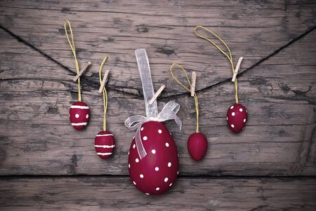Four Red Easter Eggs And One Big Dotted Red Easter Egg With A Loop And Ribbon Hanging On A Line Which Are Dotted And Striped On Brown Wooden Vintage Or Rustic Background For Easter Greetings And Happy Easter Frame photo