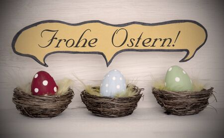 Ostern: Spotlight To Three Colorful Red Blue And Green Dotted Easter Eggs In Easter Baskets Or Nest On White Wooden Background With Comic Speech Balloon With German Text Frohe Ostern Means Happy Easter Used As Easter Decoration Or Easter Greetings Vintage Or Old