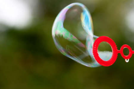 blowing bubbles: Close Up Of One Soap Bubble Which Is Blowing Up Stock Photo