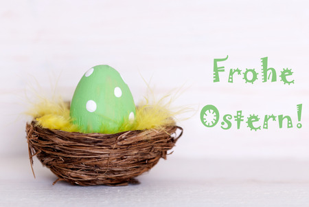 Ostern: One GreenDotted Easter Eggs In Easter Basket Or Nest On White Wooden Background With German Text Frohe Ostern Means Happy Easter As Easter Decoration Or Easter Greetings Vintage Or Old Fashion Style