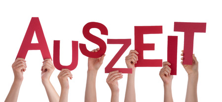 auszeit: Many Caucasian People And Hands Holding Red Letters Or Characters Building The Isolated German Word Auszeit Which Means Downtime On White Background Stock Photo