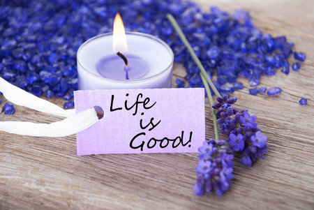 Purple Label With Candle Light And Lavender Blossoms With English Life Quote Life Is Good Wooden Background With White Ribbon photo