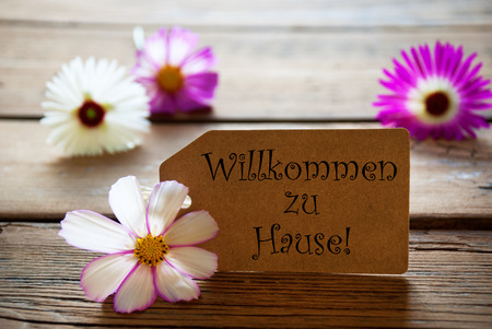 willkommen: Brown Label With German Text Willkommen Zu Hause With Purple And White Cosmea Blossoms On Wooden Background Vintage Retro Or Rustic Style