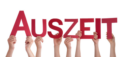 auszeit: Many Caucasian People And Hands Holding Red Straight Letters Or Characters Building The Isolated German Word Auszeit Which Means Downtime On White Background Stock Photo