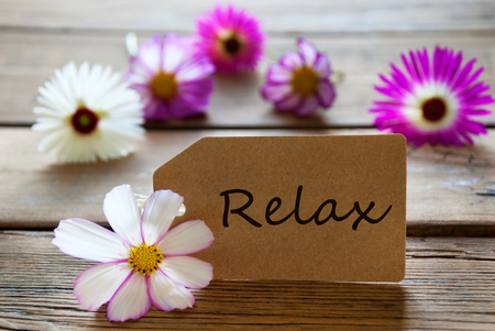 Brown Label With English Text Relax With Purple And White Cosmea Blossoms On Wooden Background Vintage Retro Or Rustic Style photo