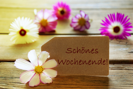 wochenende: Brown Label With Sunny Yellow Effect With German Text Sch�nes Wochenende Means Happy Weekend With Purple And White Cosmea Blossoms On Wooden Background Vintage Retro Or Rustic Style