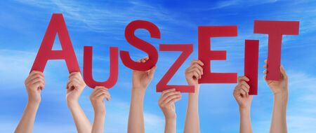 auszeit: Many Caucasian People And Hands Holding Red Letters Or Characters Building The German Word Auszeit Which Means Downtime On Blue Sky Stock Photo