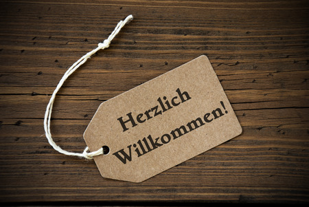 willkommen: Close Up Of A Brown Label With White Ribbon On Wooden Background With German Text Herzlich Willkommen Frame And Vintage Or Retro Style